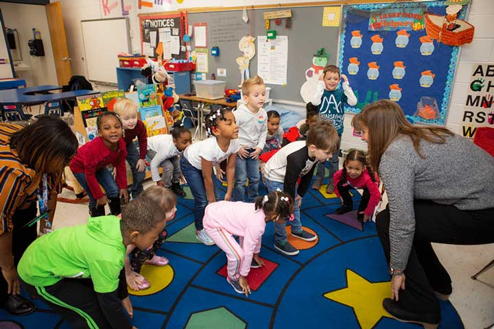 Children in preschool stretching during circle time.