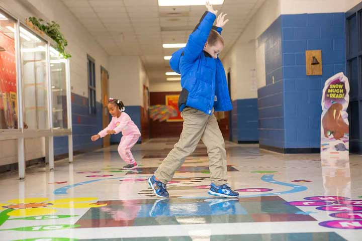 Children jumping on a letter pathway in the hall.