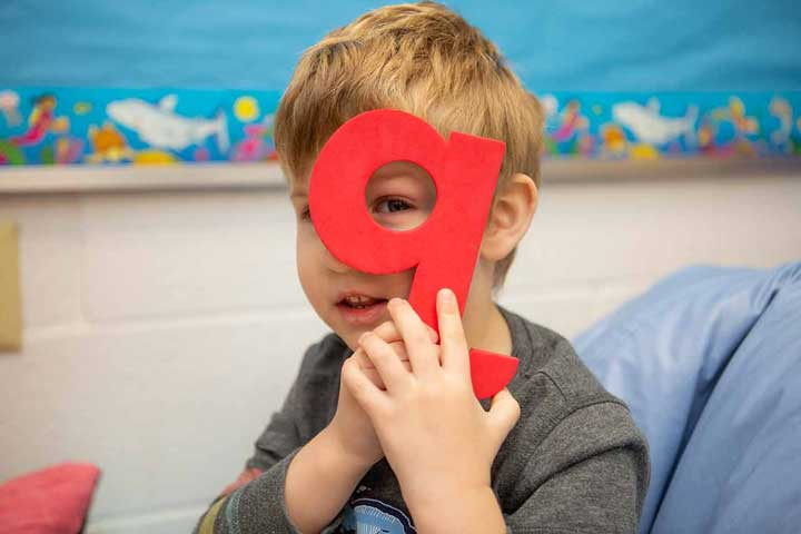 Boy holding the letter Q in front of his eye