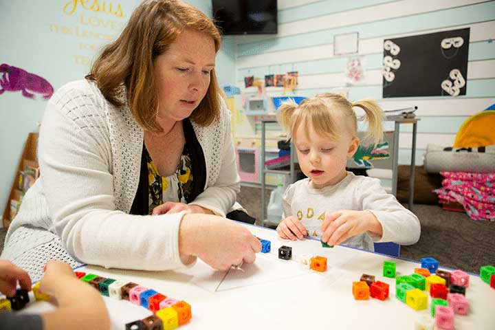 Teacher working with child using blocks and triangle shape.