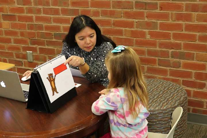 A woman administering the early mathematics assessment system to a young kindergarten girl.