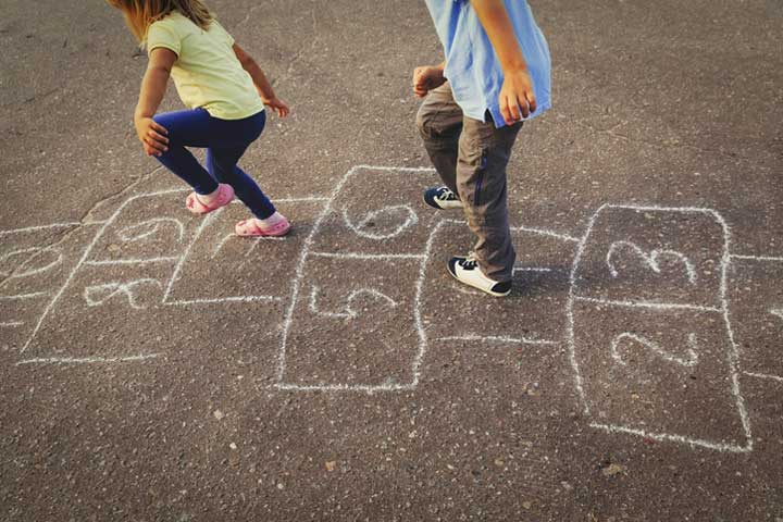 Child and parent playing hopscotch