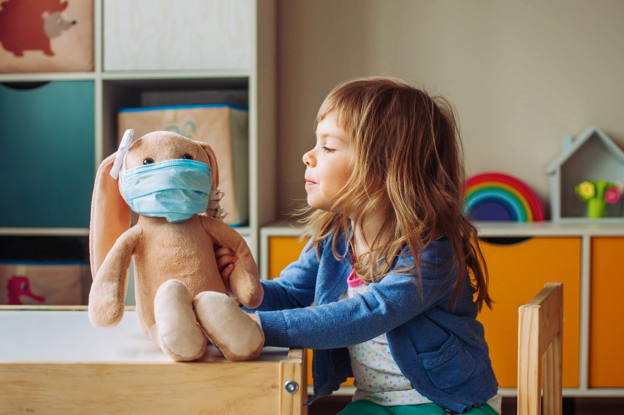 Little girl playing with rabbit soft toy in the medicine mask sitting at the table in the kids room.